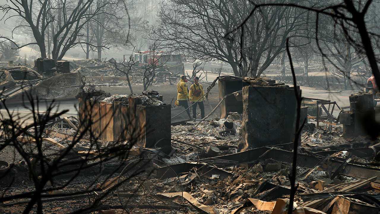 Firefighters search for human remains in a trailer park destroyed in the Camp Fire, Friday, Nov. 16, 2018, in Paradise, Calif.