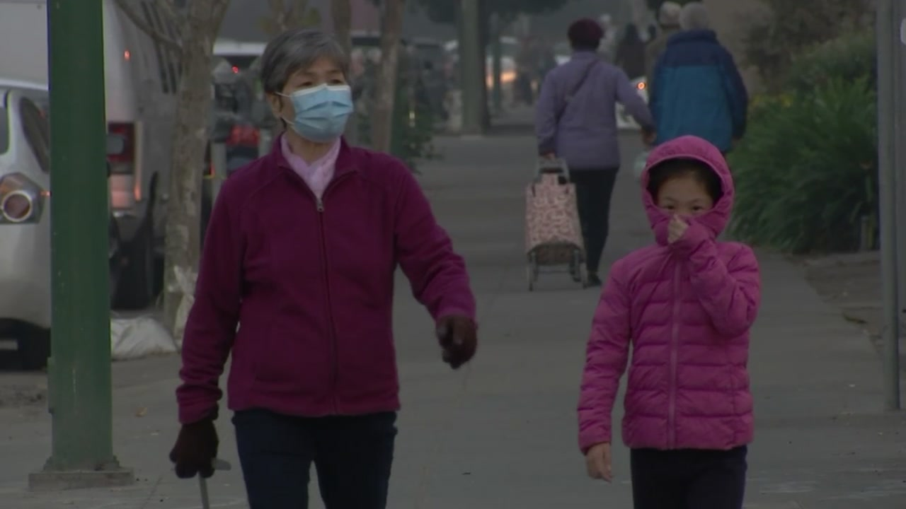 A woman and child walk through smokey skies in Berkeley, Calif. on Friday, Nov. 16, 2018.