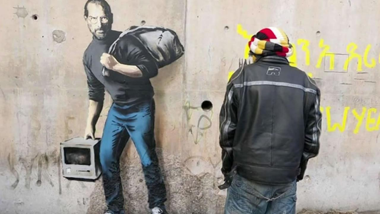 This undated image shows painting of the late Steve Jobs done by graffiti artist Banksy in Calais, France.