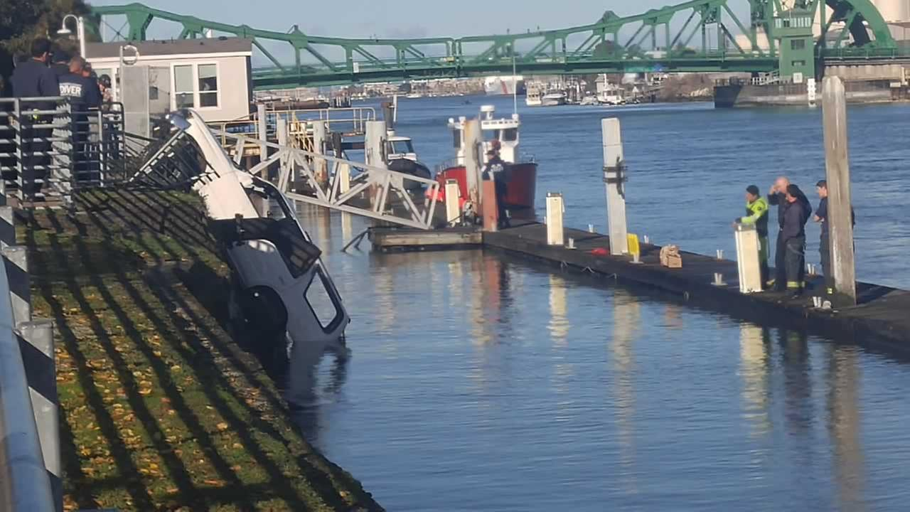 Crews work to pull this SUV from the Oakland Estuary on Saturday, December 19, 2015.