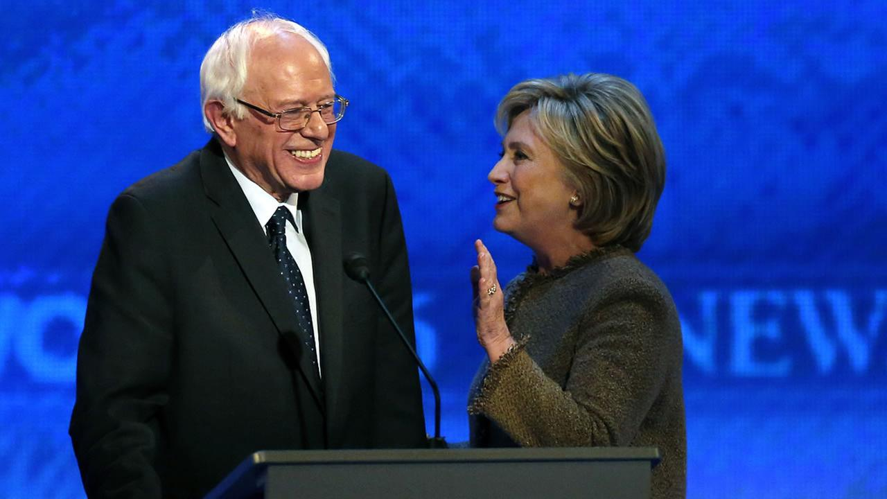 Hillary Clinton, right, speaks to Bernie Sanders during a break at the Democratic presidential primary debate Saturday, Dec. 19, 2015, at Saint Anselm College in Manchester, N.H.