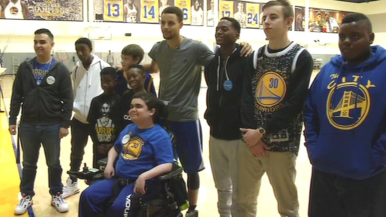 kids from Make-A-Wish foundation take photo with Steph Curry