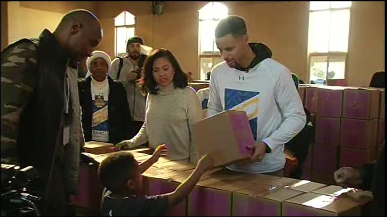 Stephen Curry and his wife, Ayesha, distribute food boxes to families in need in Oakland, Calif. on Saturday, December 26, 2015.