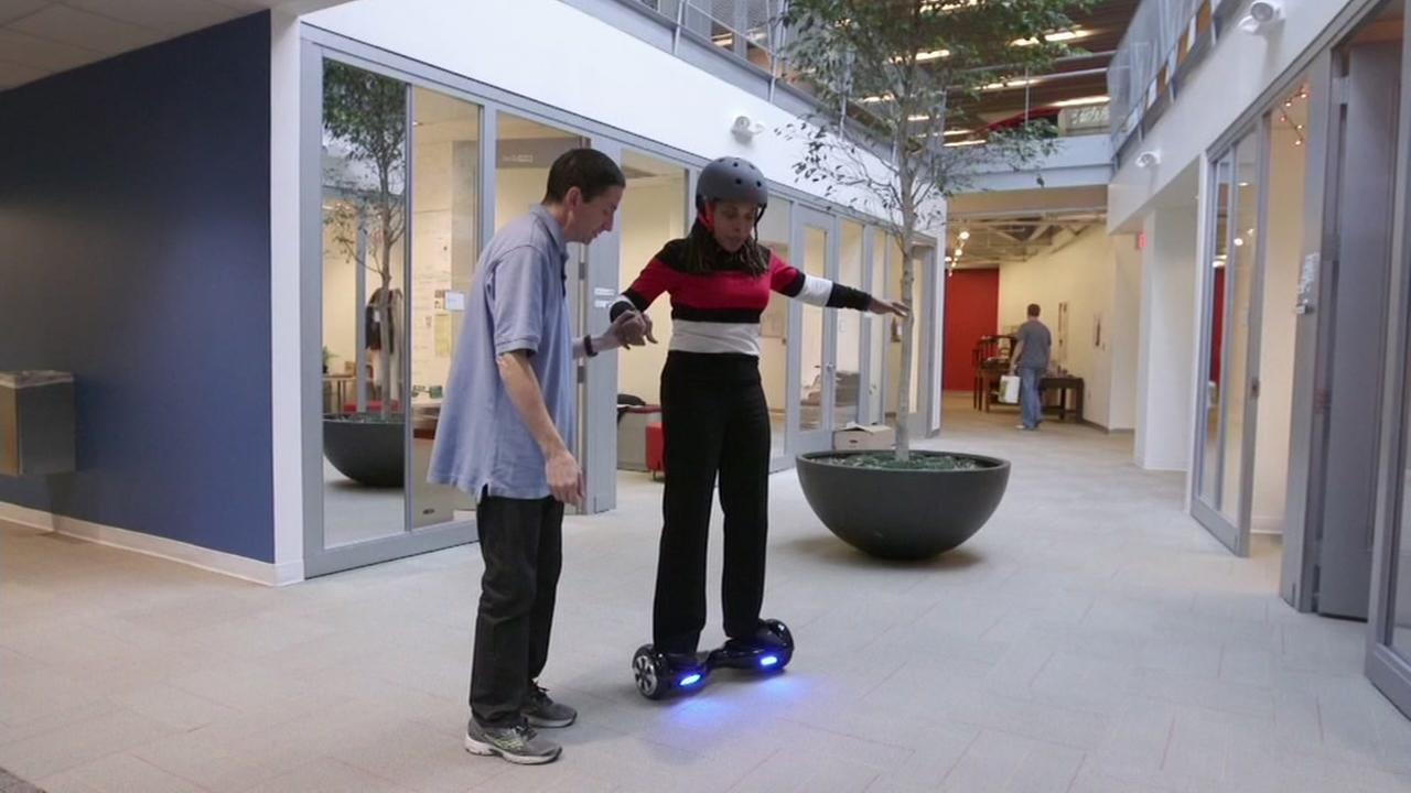 A woman needs a helping hand while testing out a hoverboard in this undated photo.