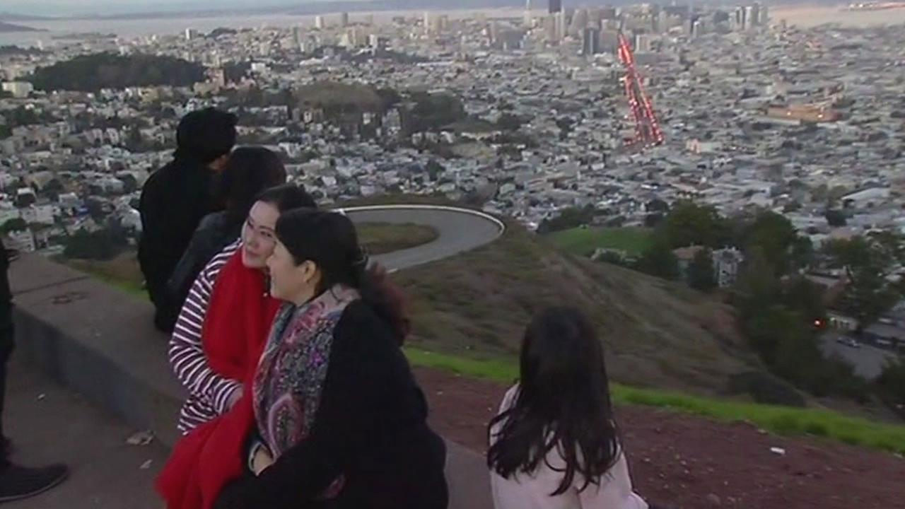 This image from Tuesday, December 29, 2015 shows tourists posing for photos at San Franciscos Twin Peaks.