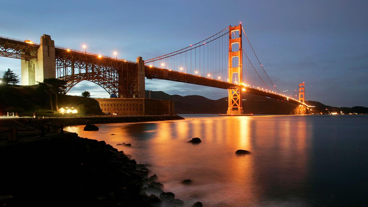 Waves crash on the pier at Fort Point as The Golden Gate Bridge lights up in the background at dusk in San Francisco, Wednesday, Feb. 4, 2009.(AP Photo/Marcio Jose Sanchez)