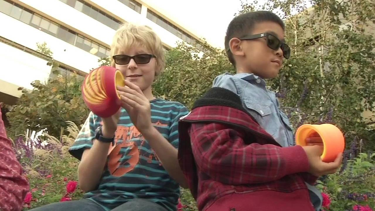 two color blind kids hold colorful plastic Slinky
