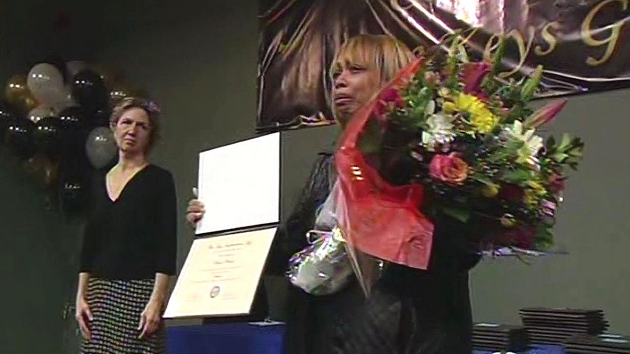 Gwen Woods accepts her sons diploma