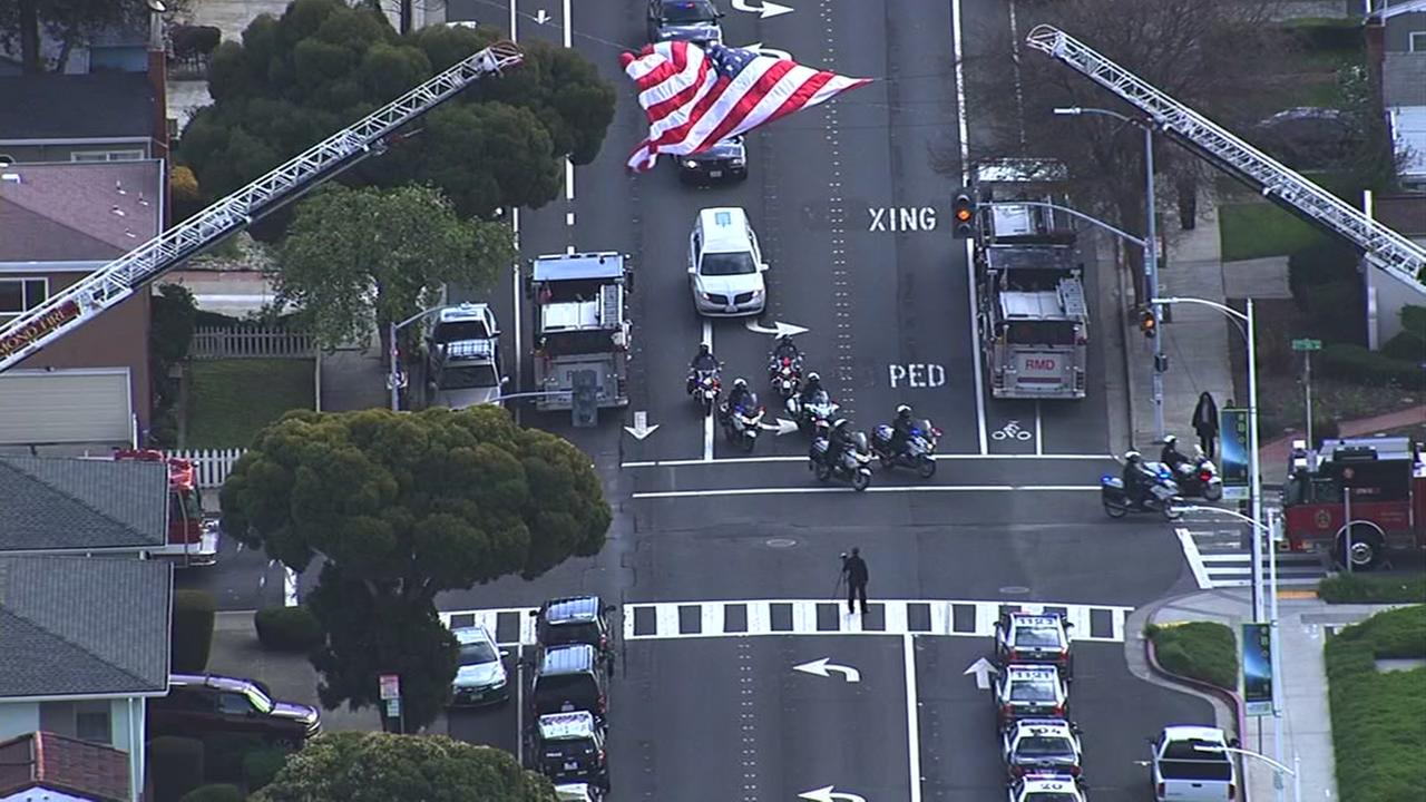 The procession for Officer Gus Vegas passes underneath an American flag in Richmond, Calif. on Friday, February 19, 2016.