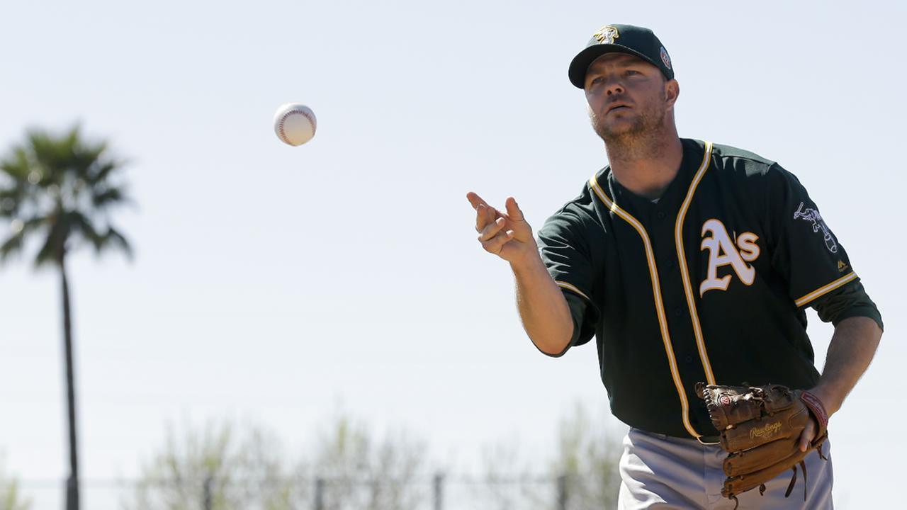 Oakland Athletics relief pitcher Ryan Madson works on a drill during spring training baseball practice in Mesa, Ariz., Sunday, Feb. 21, 2016.