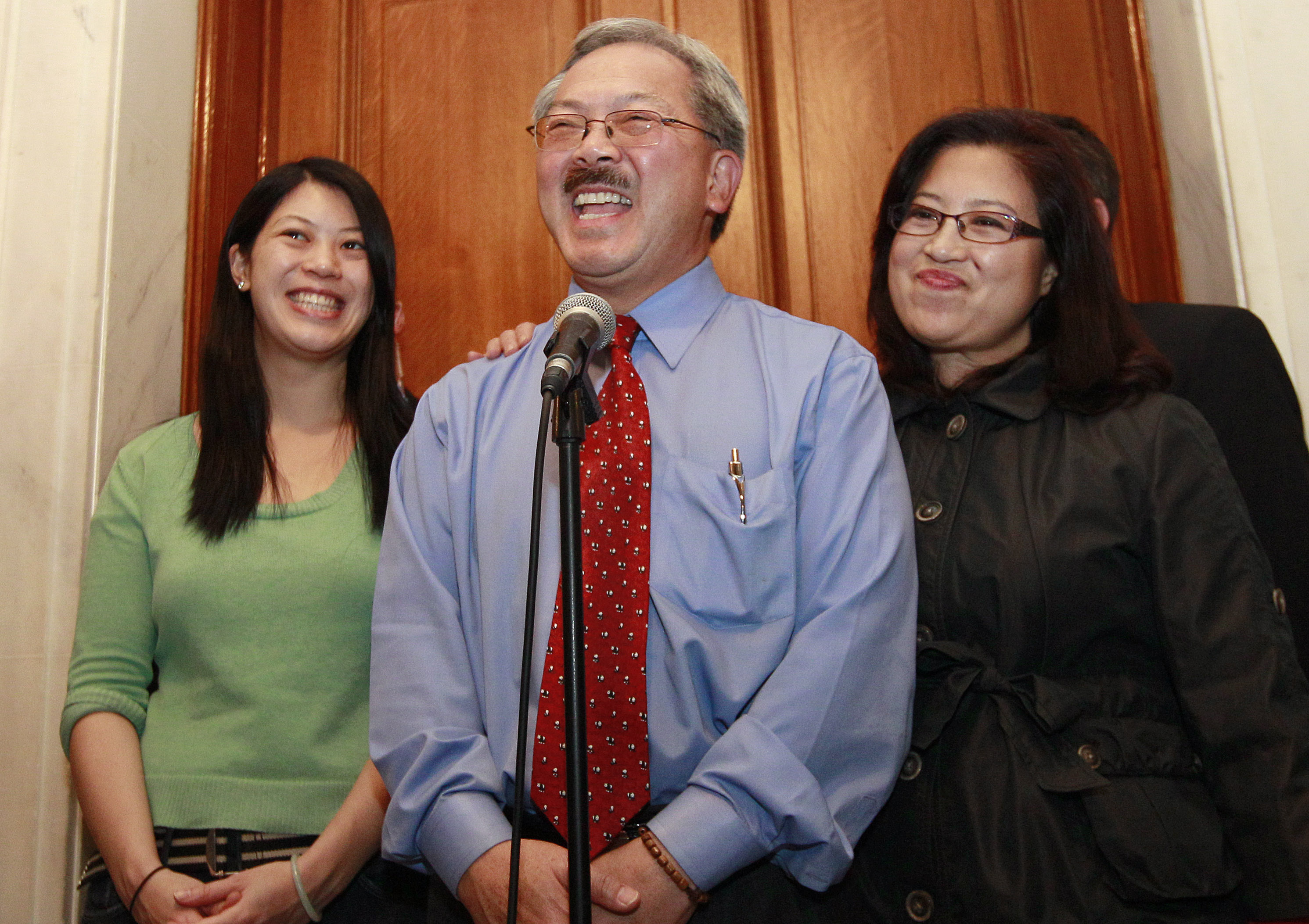 Mayor Ed Lee, center, speaks at a news conference next to his wife Anita, right, and his daughter Brianna outside of his office at City Hall, Wednesday, Nov. 9, 2011.