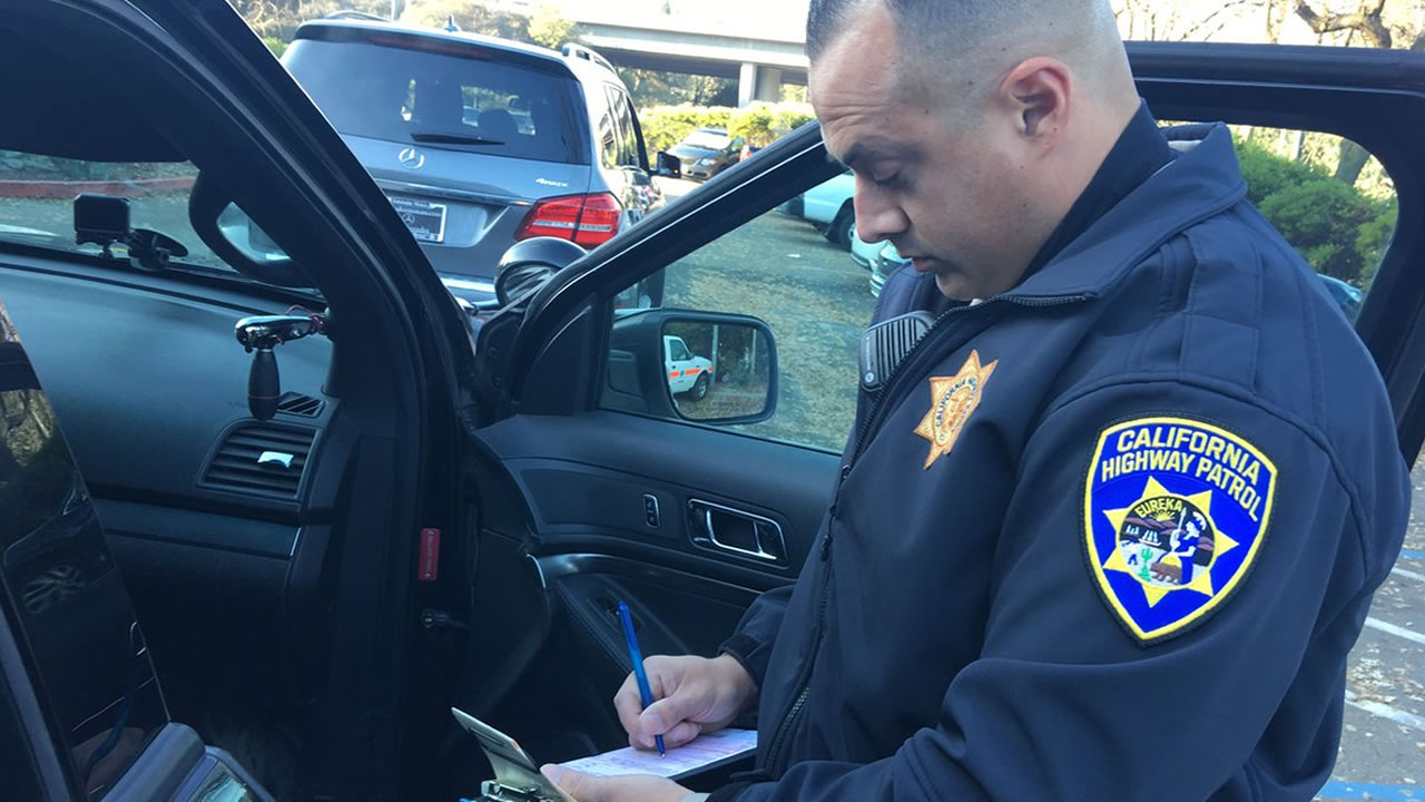 CHP Officer Chris Torrez writes a ticket for a driver in the express lane with paper plates and no transponder in Danville, Calif. on Thursday, Dec. 13, 2018.