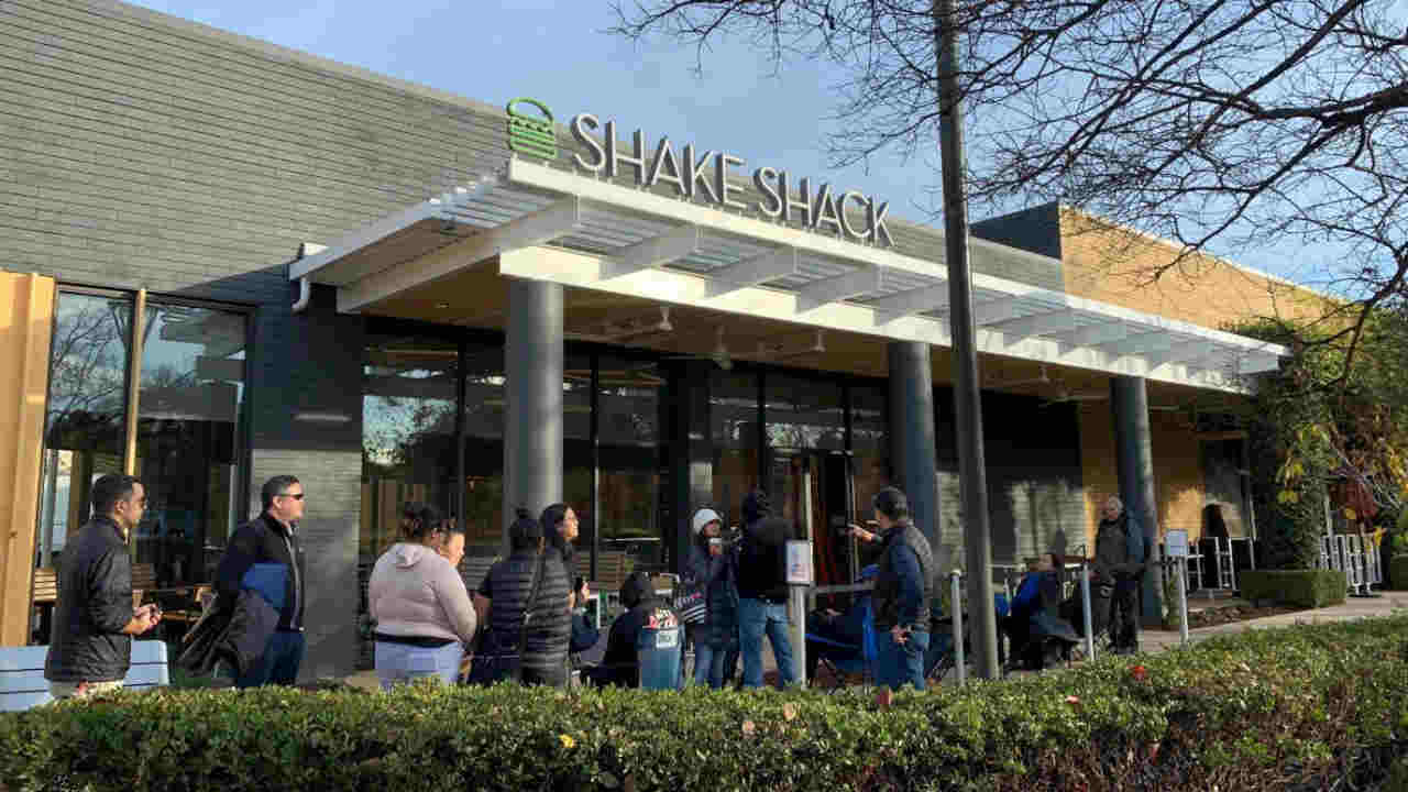 People are seen lined up ahead of a Shake Shack store opening in Palo Alto, Calif. on Saturday, Dec. 15, 2018.