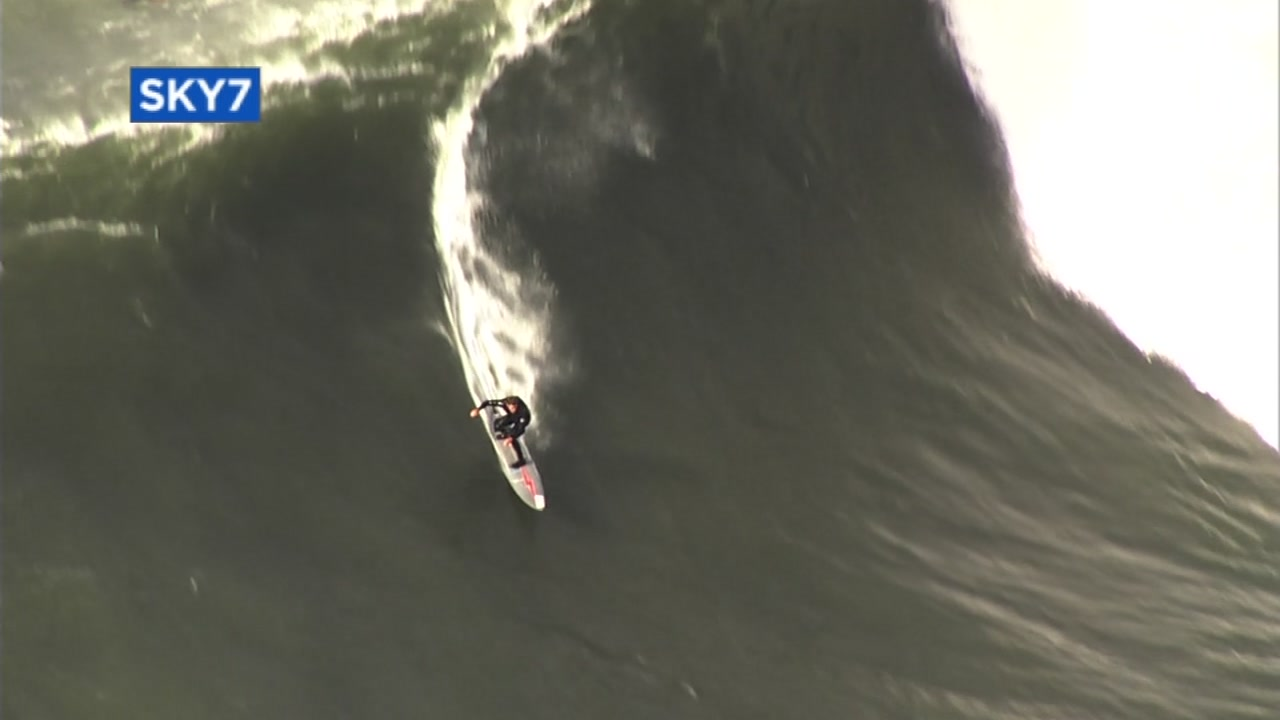 A surfer catches a big wave at Mavericks in Half Moon Bay, Calif. on Monday, Dec. 17, 2018.