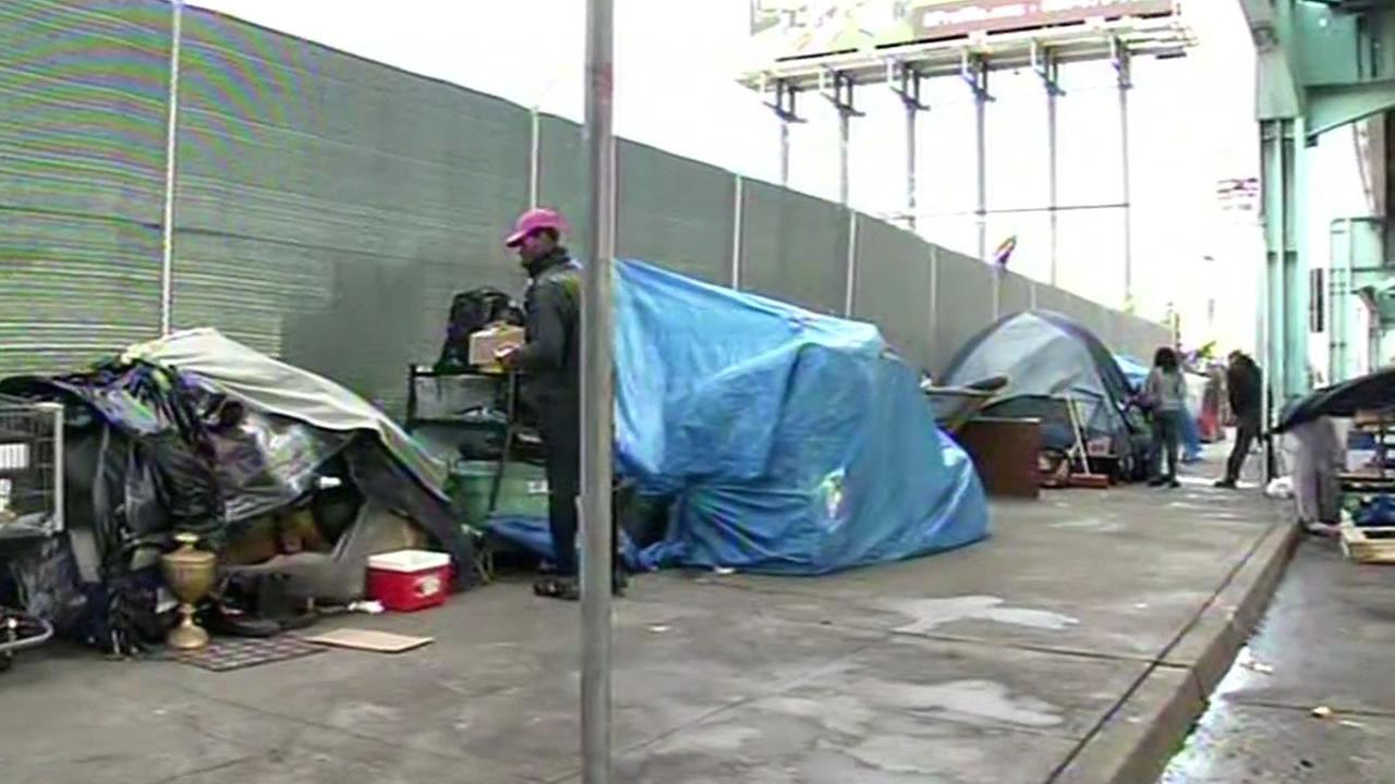 homeless tents line up under Highway 101 bridge