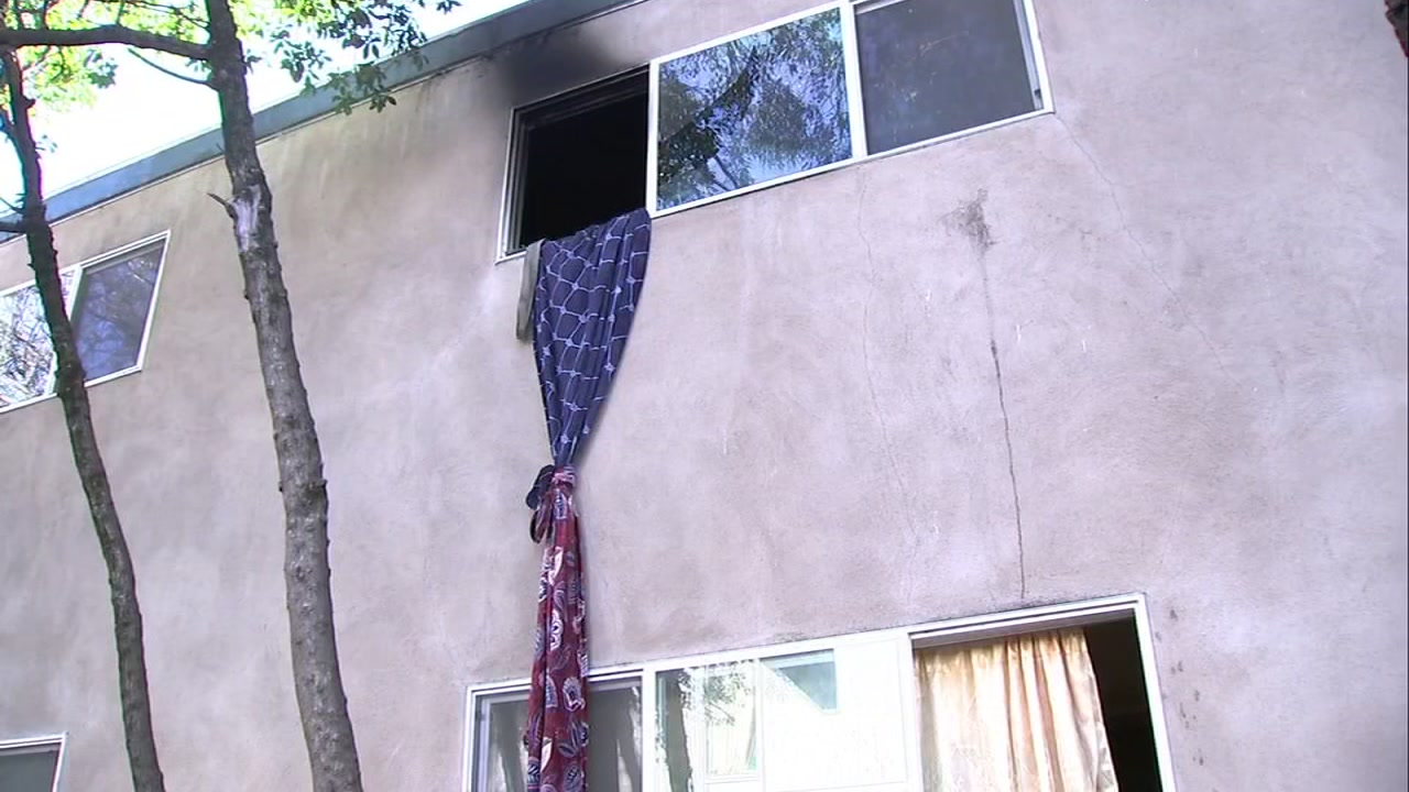 Bed sheets hang out a window of an apartment complex in San Rafael after a father and son use them to escape the flames. Dec. 26, 2018