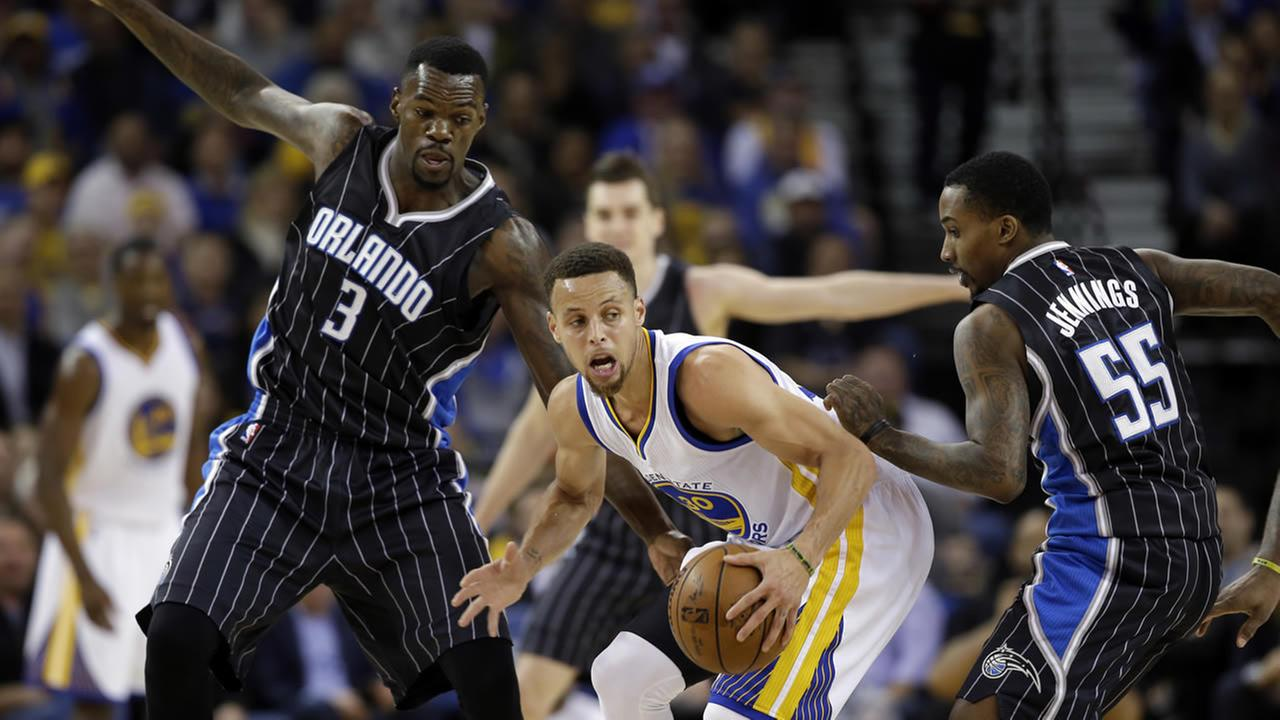 Warriors Stephen Curry is defended by Magics Dewayne Dedmon during an NBA basketball game Monday, March 7, 2016, in Oakland, Calif. (AP Photo/Marcio Jose Sanchez)