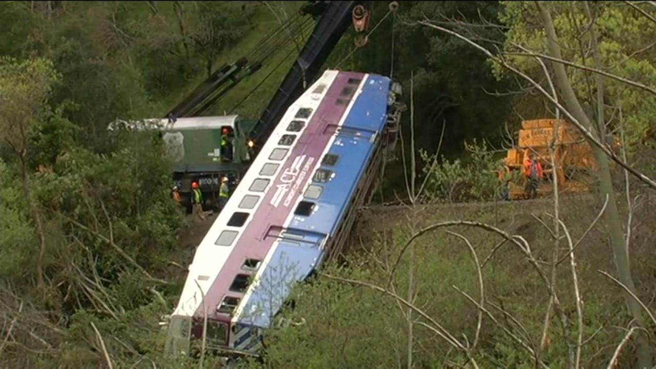 Crews work to remove a derailed ACE train car from an embankment on Tuesday, March 8, 2016 in Sunol, Calif.