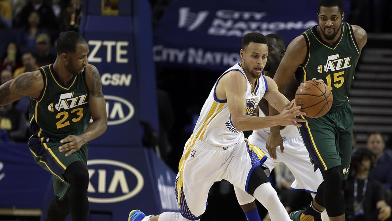 Warriors Curry drives the ball between Jazzs Johnson and Favors during the first half of an NBA basketball game on March, 9, 2016 in Oakland, Calif. (AP Photo)