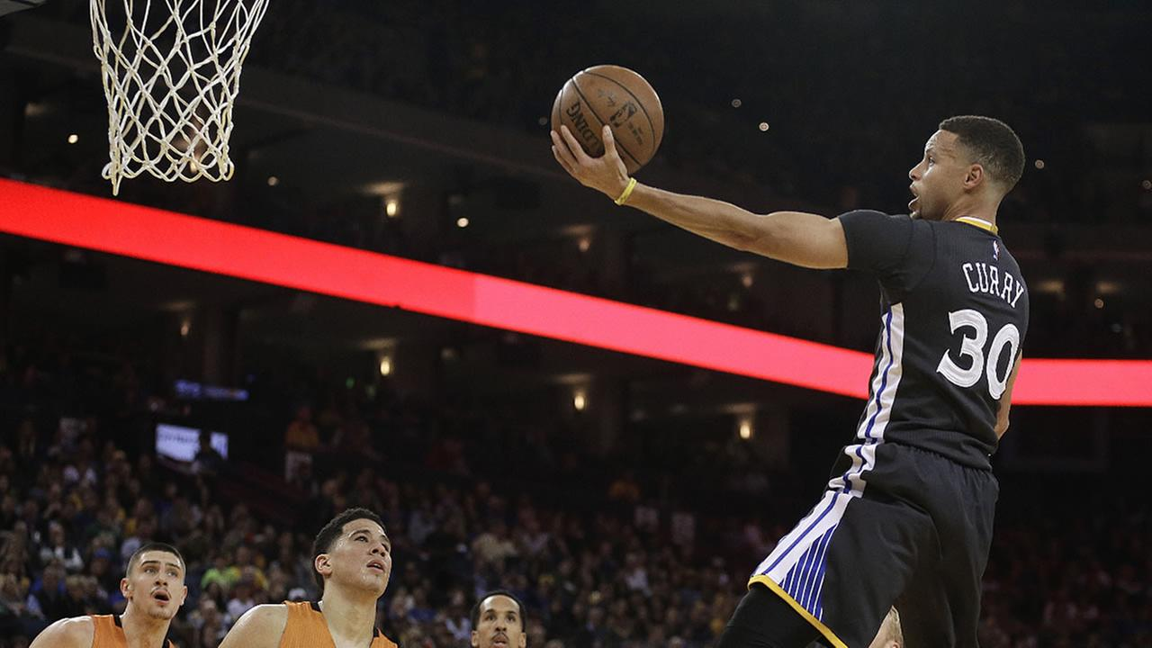 Golden State Warriors Stephen Curry lays up a shot against the Phoenix Suns during the first half of their game on Saturday, March 12, 2016, in Oakland, Calif.
