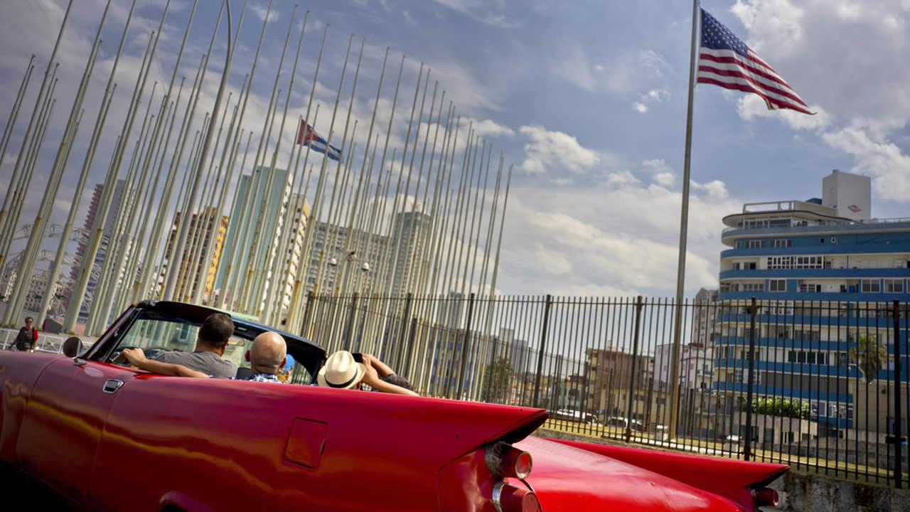 Tourists ride a vintage American convertible as they drive next to the American flag and a Cuban flag at the United States embassy in Havana, Cuba, Friday, March 18, 2016.