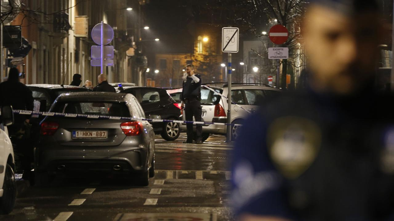 Police guard a check point and man positions during a police raid in the suburb of Schaerbeek in Brussels, early Friday, March, 25, 2016.