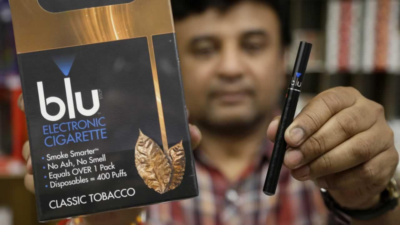 Sales clerk Sam Patel, of Waltham, Mass., displays a blu e-cigarette, right, and a container of the e-cigarettes, left, at a shop, Wednesday, May 21, 2014, in Brookline, Mass.