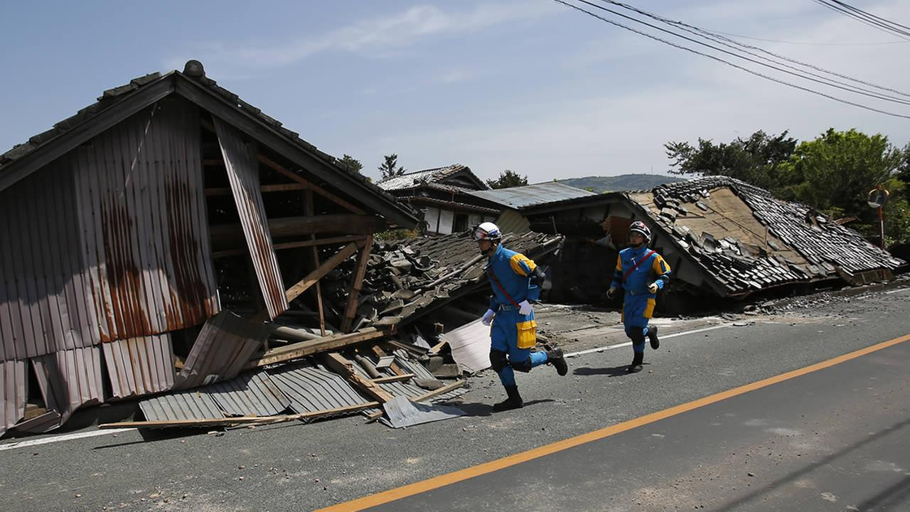 Police officers run in front of collapsed houses in Mashiki, Kumamoto prefecture, southern Japan, Friday, April 15, 2016.. (AP Photo/Koji Ueda)