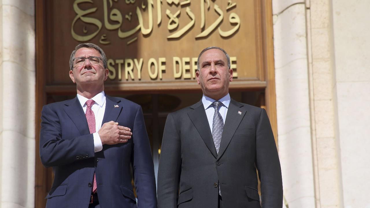 U.S. Defense Secretary Ash Carter his Iraqi counterpart Khaled al-Obeidi stand for their countrys national anthems at the Ministry of Defense, Baghdad, Iraq, Mon., April 18, 2016.