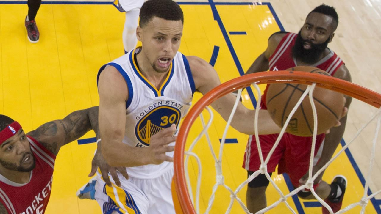 Golden State Warriors Stephen Curry, center, drives past Houston Rockets Josh Smith, left, and James Harden, bottom right, during the first half in Game 1 of a first-round NBA basketball playoff series Saturday, April 16, 2016, in Oakland, Calif. (Kyle
