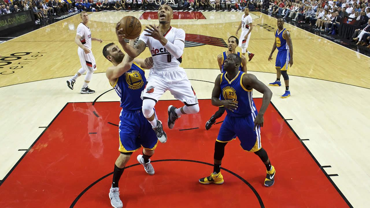 Portland Trail Blazers guard Damian Lillard shoots over Golden State Warriors center Andrew Bogut, left, and forward Draymond Green, right, in Game 3 of second-round NBA playoff series Saturday, May 7, 2016, in Portland, Ore.