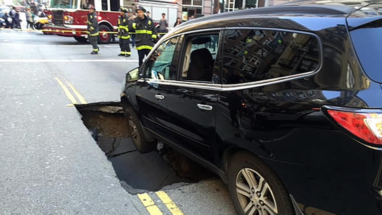 A car is seen stuck inside of a large sinkhole after it opened up in San Francisco, Calif. on Monday, May 10, 2016.