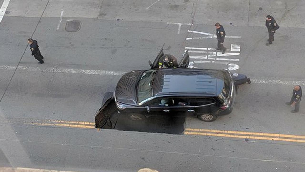 Crews rescued a family inside a  car that got stuck in a large sinkhole in downtown San Francisco, on Tuesday, May 10, 2016.
