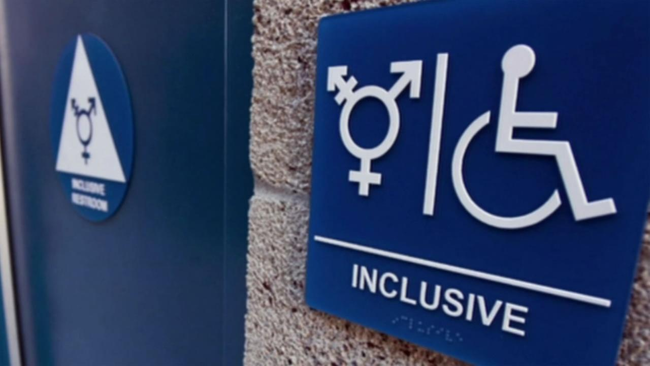 A sign hangs outside of a gender-inclusive public restroom.