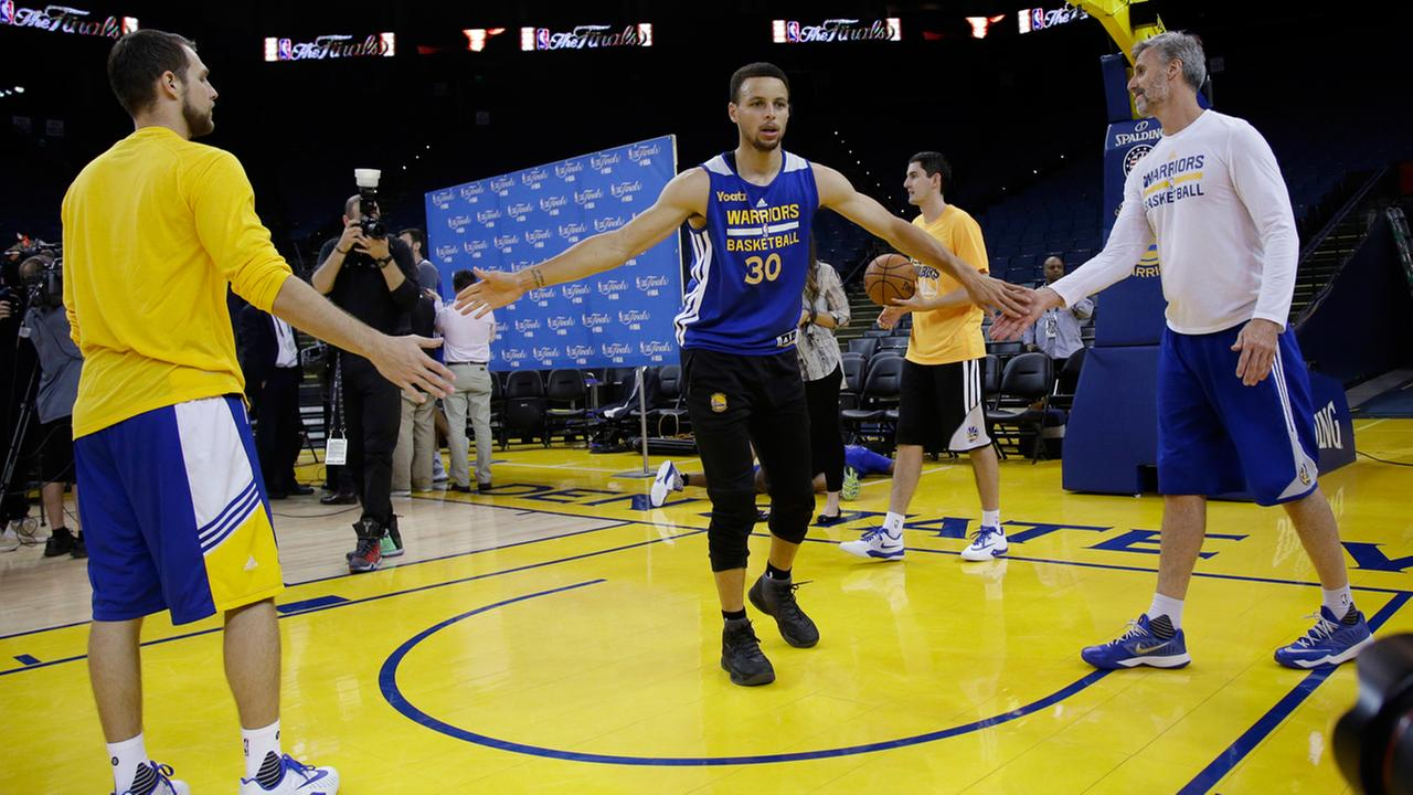 Golden State Warriors Stephen Curry, center, slaps hands with staff members during NBA basketball practice Wednesday, June 1, 2016, in Oakland, Calif.