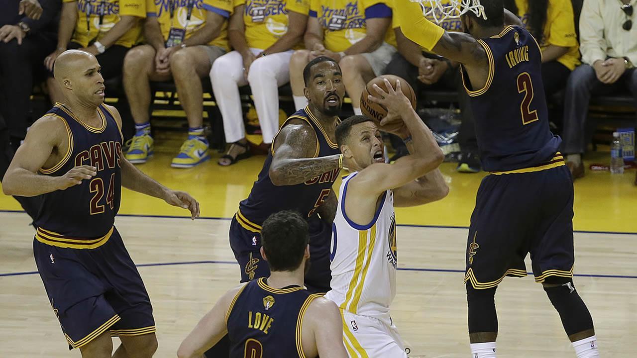 Warriors Stephen Curry shoots between Cavaliers defenders during Game 2 of basketballs NBA Finals in Oakland, Calif., on June 5, 2016. (AP Photo/Marcio Jose Sanchez)