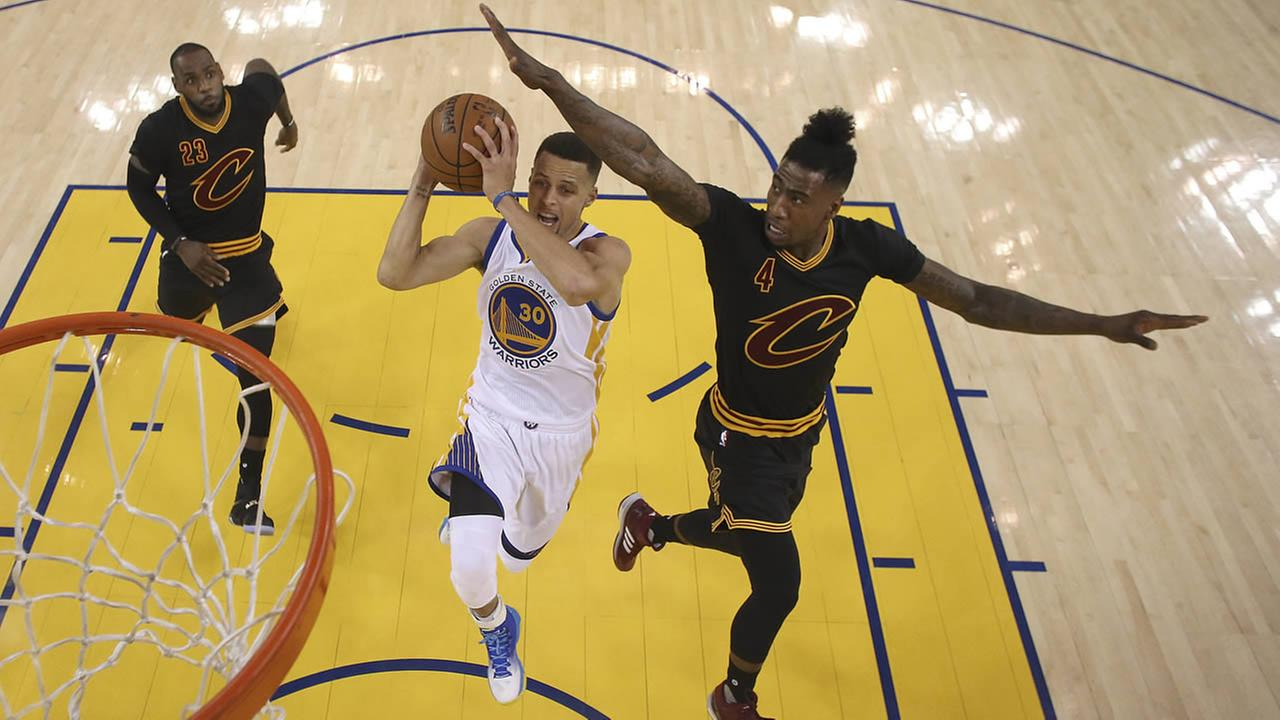 Warriors Curry shoots between Cavaliers James and Shumpert  during Game 5 of basketballs NBA Finals in Oakland, Calif., on June 13, 2016. (Ezra Shaw/Getty Images via AP, Pool)