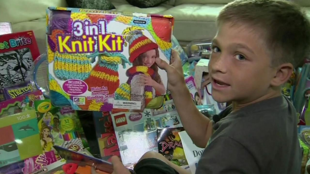 This image shows 10-year-old Kadin Hoven with a pile of toys after launching a toy drive for Mattel Childrens Hospital at UCLA, the same hospital where he is receiving treatment.