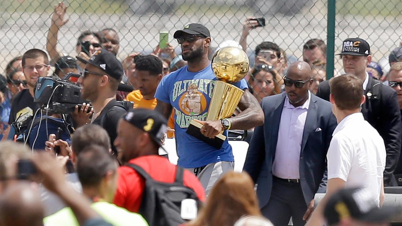 Cleveland Cavaliers LeBron James carries the NBA Championship trophy after arriving in Cleveland, Monday, June 20, 2016.
