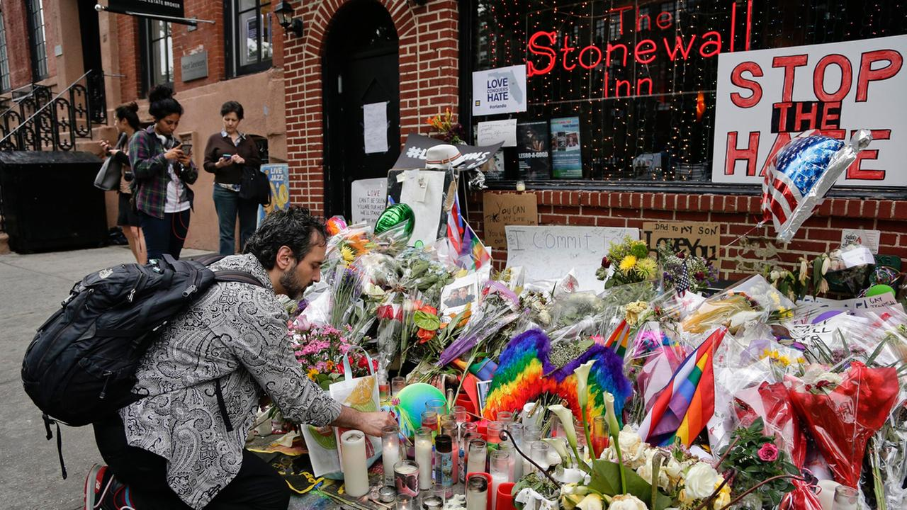 FILE - In this June 16, 2016 file photo, a man lights candles on a memorial outside the Stonewall Inn for victims of the Orlando Shooting, in New York.