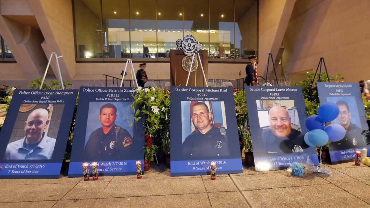 Portraits of the five fallen police officers sit in front of a stage after a candle light vigil in front of city hall honoring them, Monday, July 11, 2016, in Dallas.