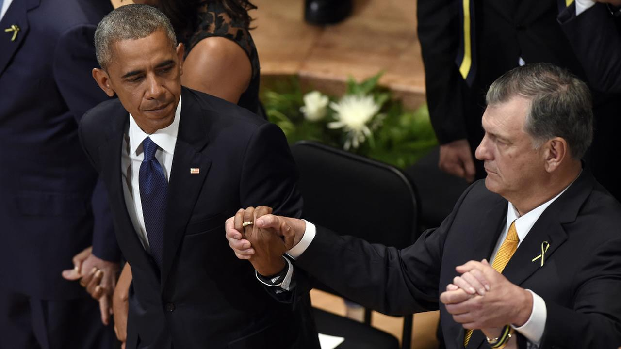 resident Barack Obama holds hands with Dallas Mayor Mike Rawlings during a memorial service for the fallen police officers at the in Dallas, July 12, 2016.