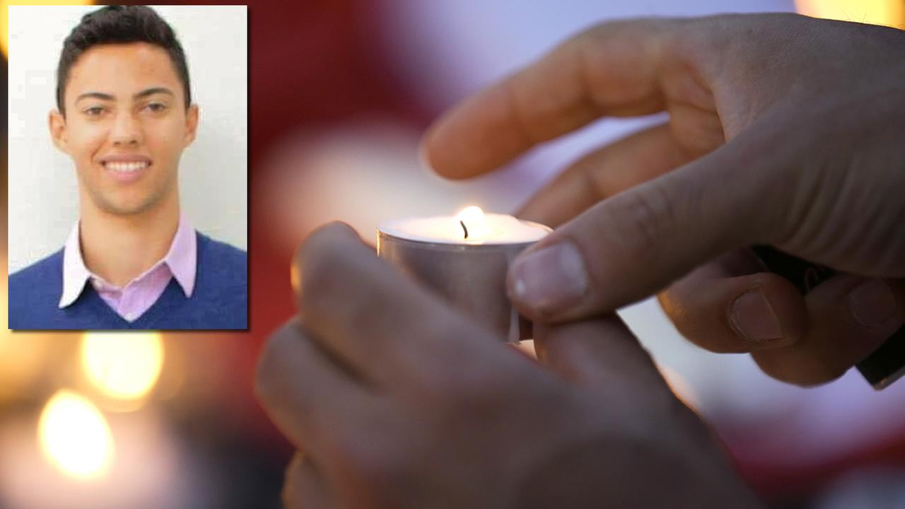 A man lights a candle while paying tribute to the victims of a truck attack in the French resort city of Nice, southern France, Friday, July 15, 2016. (AP Photo/Luca Bruno)