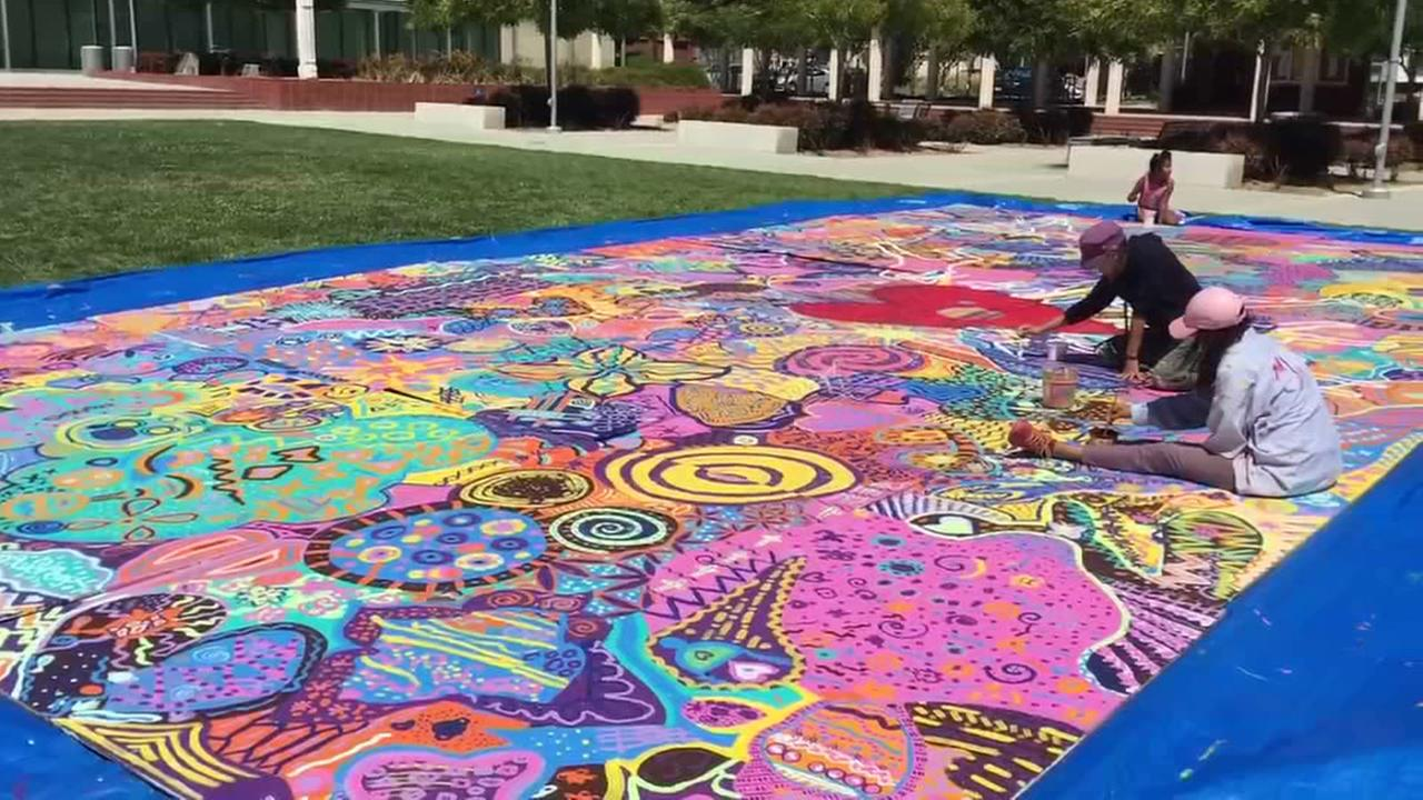 People are seeing working on a community mural in Richmond, Calif. on Friday, July 22, 2016.