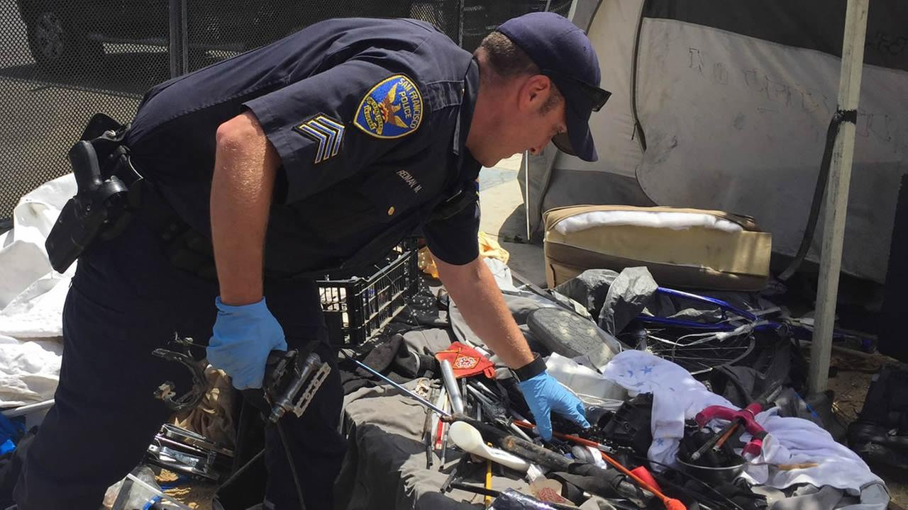 A San Francisco police officer looks through stolen bike parts on Monday, August 15, 2016.