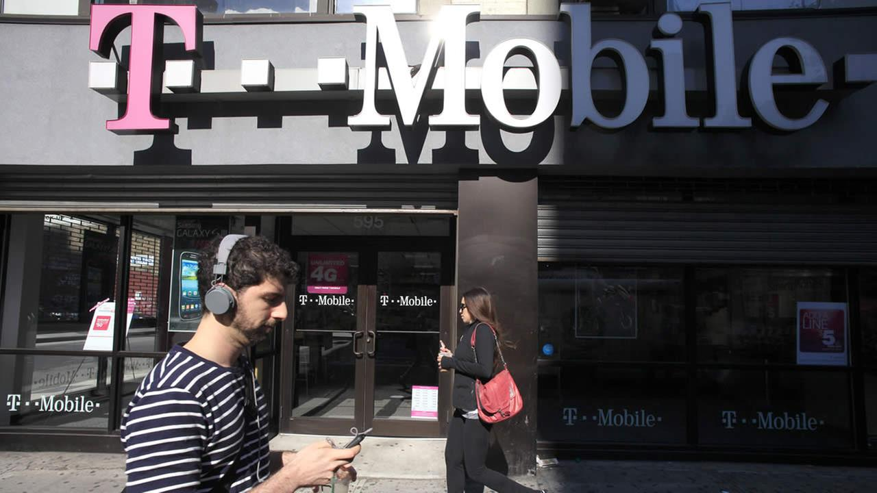 This Sept. 12, 2012 file photo shows a man using a cellphone as he passes a T-Mobile store in New York. (AP Photo/Mark Lennihan, File)