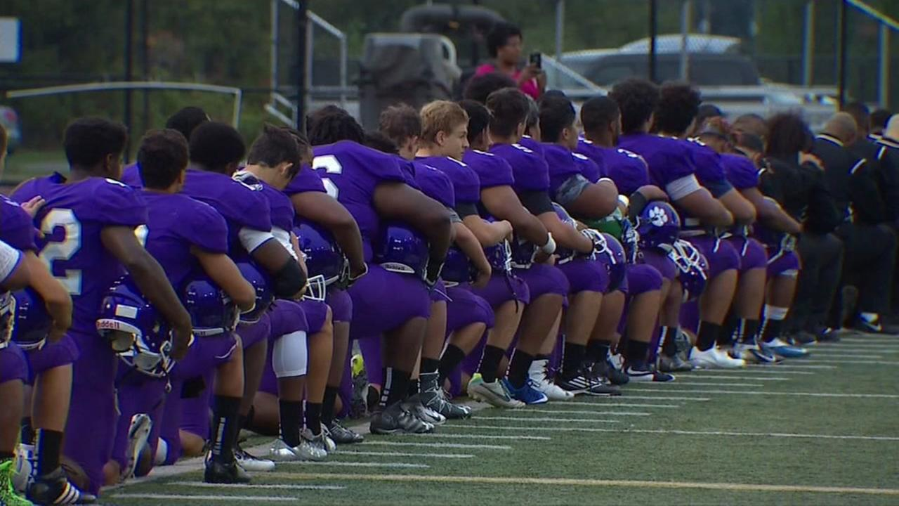 Students at Garfield High School in Seattle kneel during the national anthem on Friday, September 16, 2016.