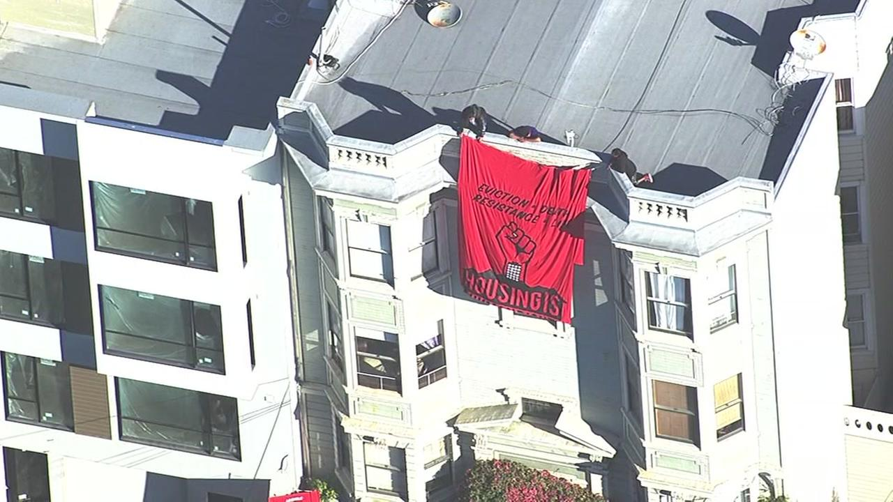 Protesters work to hang a banner from 100-year-old Iris Canadas home in San Francisco on Thursday, September 22, 2016.