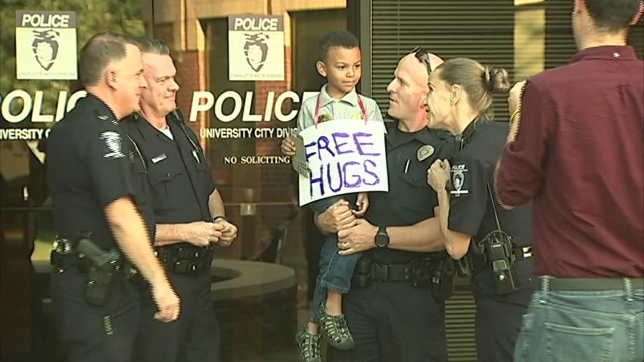 This image shows five-year-old Jayden Hooker giving out free hugs to police officers in North Carolina.