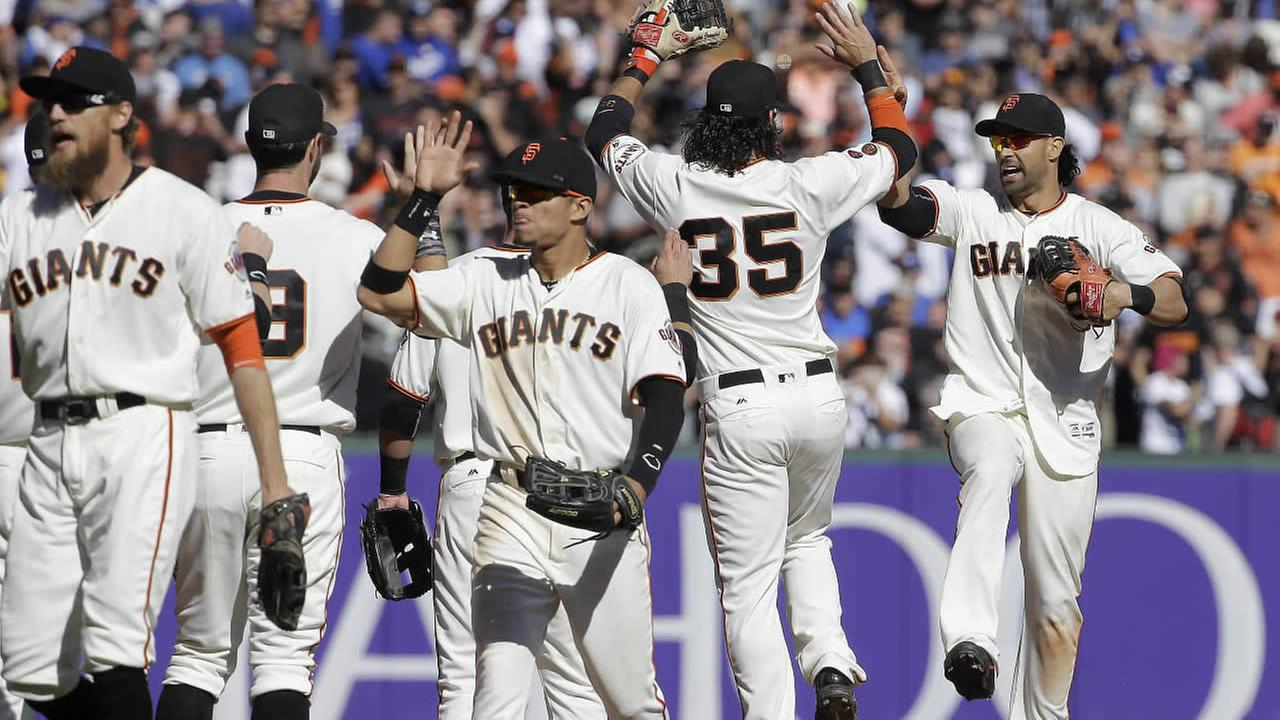 San Francisco Giants shortstop Brandon Crawford (35) and left fielder Angel Pagan, right, celebrate with teammates after they defeated the Los Angeles Dodgers in a baseball game in San Francisco, Saturday, Oct. 1, 2016.